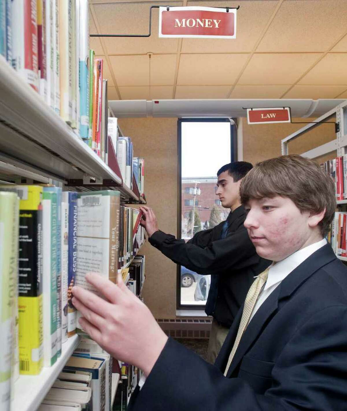 Danbury High School juniors Chris DelDebbio and Matt Hanrahan select books from the Money section of Danbury Public Library for a financial literacy display at the library as part of their project to reach out. Monday, Jan. 31, 2011