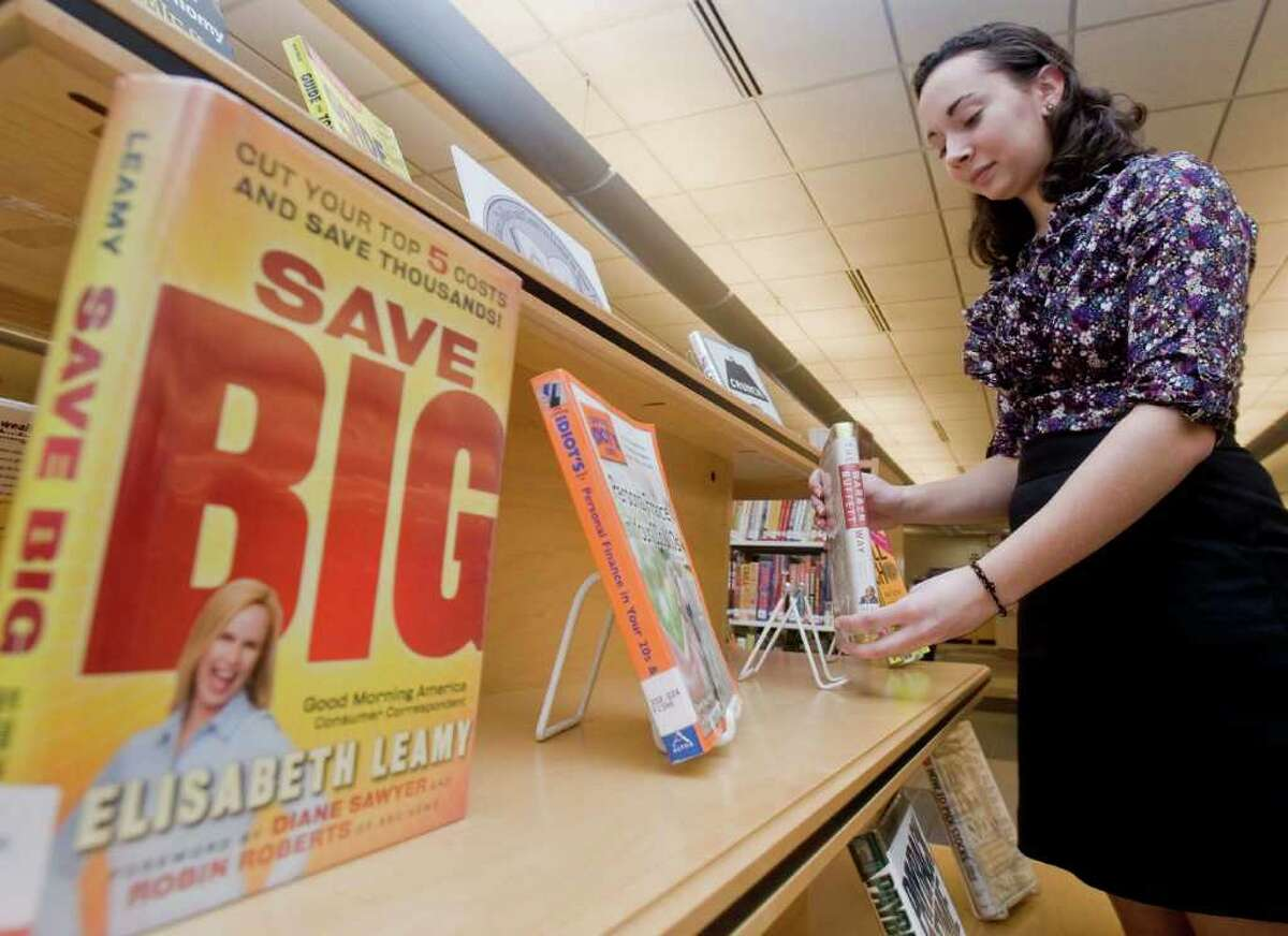 Danbury High School junior Mary Sigillo adjusts one of 17 financial books on display at Danbury Pulblic Library to help promote knowledge and responsibility with money. Monday, Jan. 31, 2011