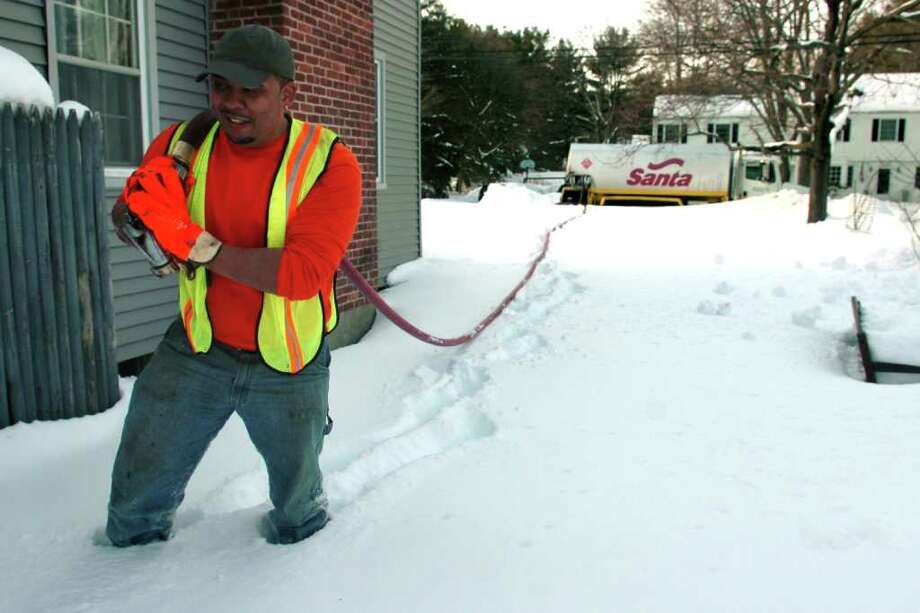 Miles Ballew from Santa Fuel trudges through snow up to his knees as he delivers heating oil to a home on Mill River Rd. in Fairfield, Conn. Jan. 31st, 2011. Photo: Ned Gerard / Connecticut Post