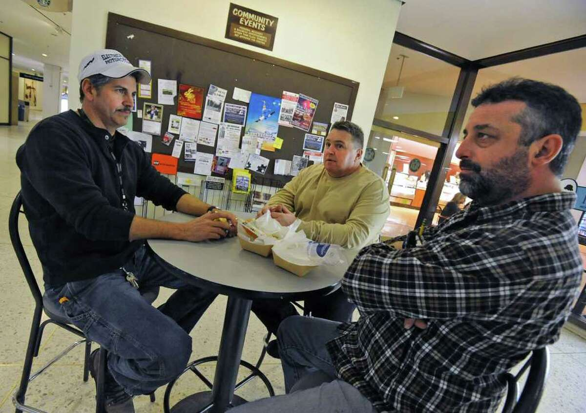 From left, electrician Steve Ringwood of Kinderhook, electrician Bryan Hanley of Saratoga Springs and pipe fitter Chris Hagadorn of Melrose finish eating their lunches outside the main cafeteria at the Empire State Plaza in Albany, NY, on January 31, 2011. The men are all contracted vendors for the state and fear that their jobs will be cut in the governor's budget, which will be announced Tuesday. (Lori Van Buren / Times Union)