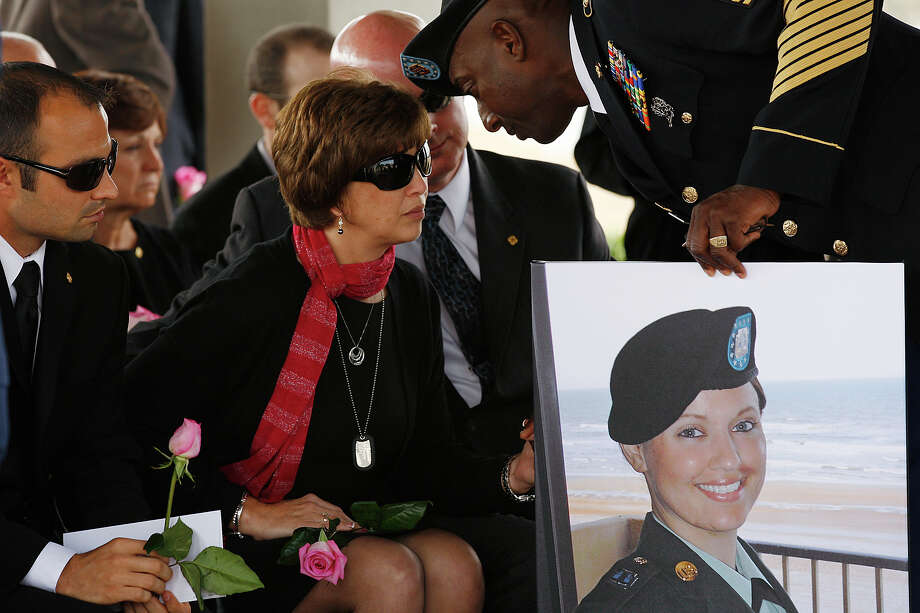 Casualty Assistance Officer Master Sgt. Wilfred Bedeau holds a photo of Army Sgt. Amanda Older Downing, 24, as he talks to her mother, Karen Martin, at a service Monday for Downing at Fort Sam Houston National Cemetery. The Iraq War veteran and Madison High graduate died Jan. 22 of cancer that her family said was a result of the war. Holding the flower at left is her husband, Andrew. Photo: Jerry Lara/glara@express-news.net