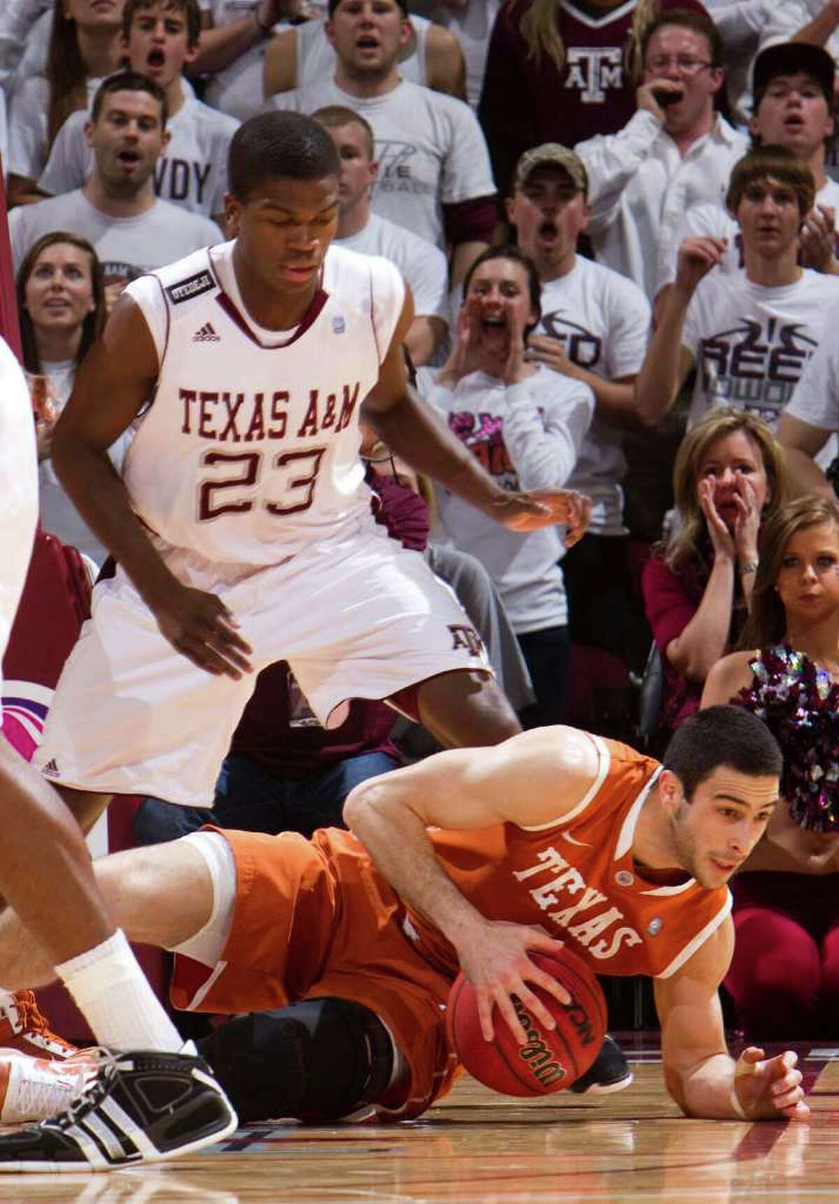 Texas guard Dogus Balbay (bottom) dives for the ball against Texas A&M defender Naji Hibbert during the first half on Monday, Jan. 31, 2011, in College Station.