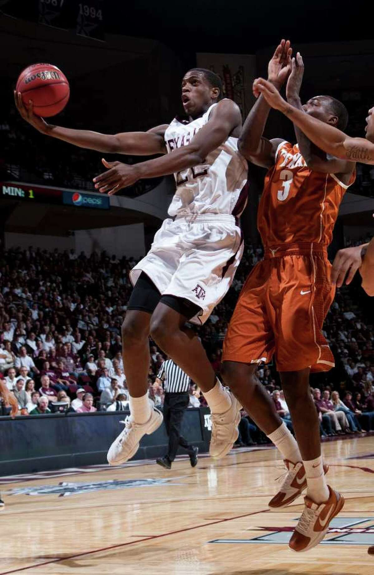Texas A&M's Khris Middleton shoots against Texas' Jordan Hamilton during the first half on Monday, Jan. 31, 2011, in College Station.