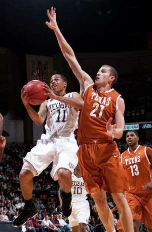 Texas A&M guard B.J. Holmes goes for a shot against Texas' Matt Hill during the first half on Monday, Jan. 31, 2011, in College Station. Photo: JON EILTS, ASSOCIATED PRESS