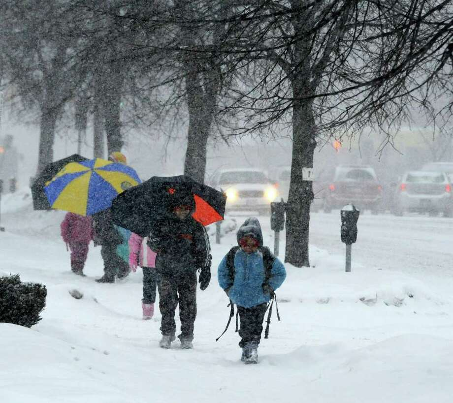 The Kaurejo family heads for school Tuesday during the first of two snowstorms forecast for over the next two days. (Skip Dickstein / Times Union) Photo: SKIP DICKSTEIN / 2008