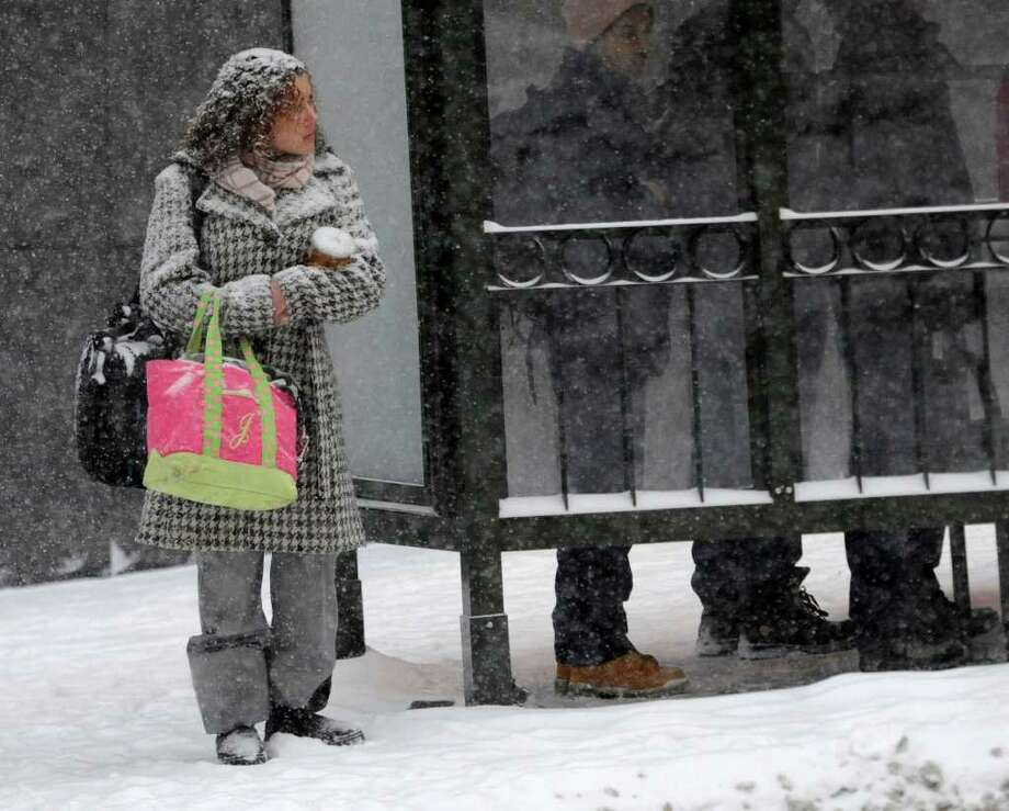 Snow clings to a pedestrian Tuesday as she waits to cross Washington Avenue in Albany. (Skip Dickstein / Times Union) Photo: SKIP DICKSTEIN / 2008