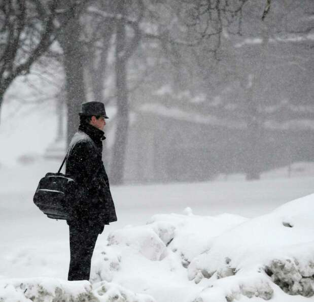 Snow falls on a pedestrian Tuesday as he waits to cross Washington Avenue in Albany. (Skip Dickstein