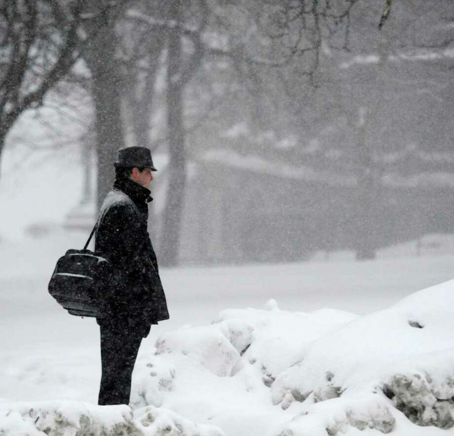 Snow falls on a pedestrian Tuesday as he waits to cross Washington Avenue in Albany. (Skip Dickstein / Times Union) Photo: SKIP DICKSTEIN / 2008