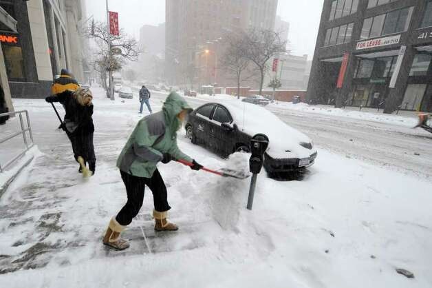 Teri Gile, foreground, and Wendy Mueller, of the Gordon Co., remove snow Tuesday from the sidewalk on lower State Street in Albany. (Skip Dickstein / Times Union) Photo: SKIP DICKSTEIN