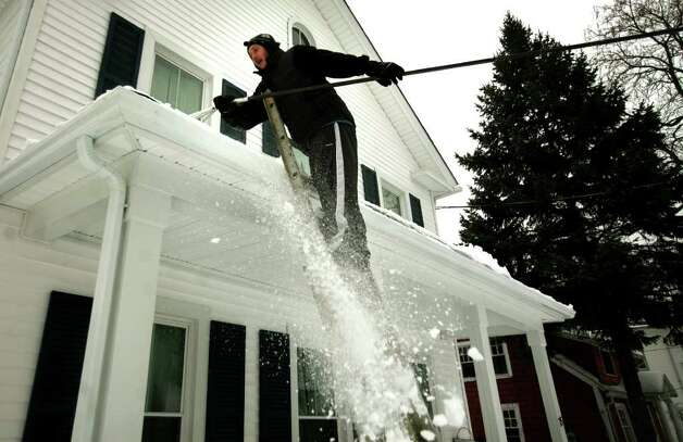 Seann Lisi of Milford uses a roof rake to clear snow from the porch roof of a home on Lafayette Street in Milford on Tuesday, February 1, 2011. Photo: Brian A. Pounds / Connecticut Post