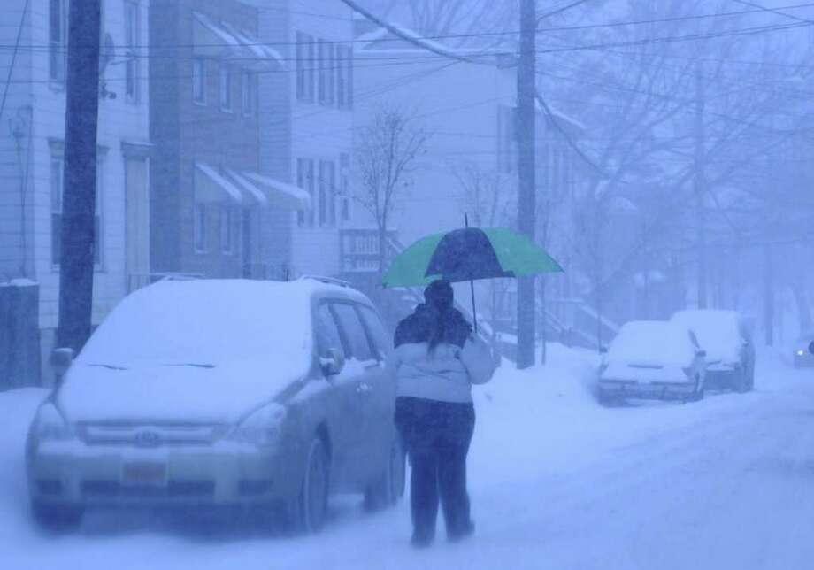 A woman uses an umbrella to keep the snow off of her Tuesday as she walks down Livingston Avenue in Albany. (Paul Buckowski / Times Union) Photo: Paul Buckowski / 00011944A