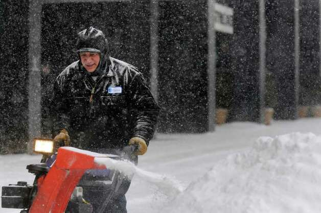 Maintenance worker Ariel Ruiz uses a snowblower Tuesday at Carrow Real Estate Services in Albany. He said it was his fifth time clearing snow since 6 a.m., and it wasn't even noon yet. (Cindy Schultz / Times Union) Photo: Cindy Schultz