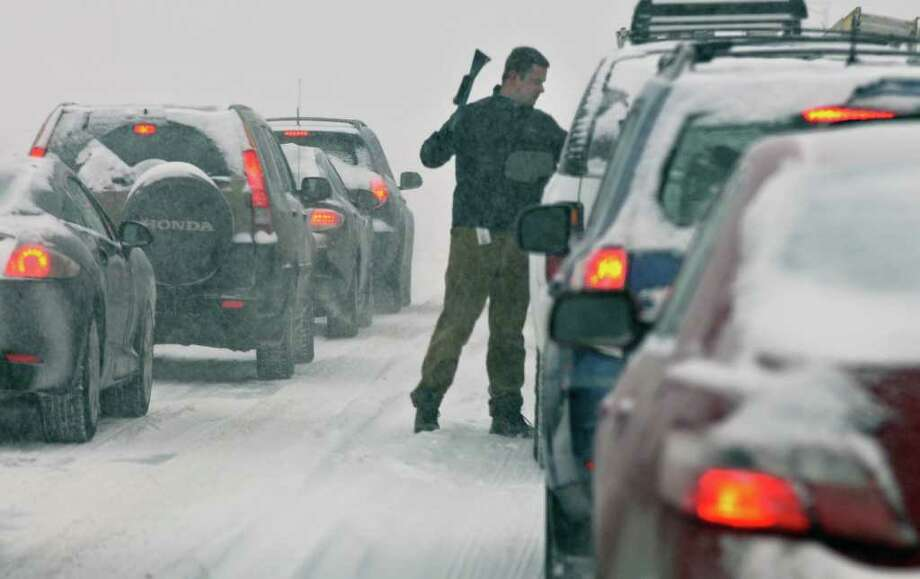 A motorist scrapes the windshield Tuesday as he waits for a red light on Route 9 in Colonie. (John Carl D'Annibale / Times Union) Photo: John Carl D'Annibale / 0202_weather