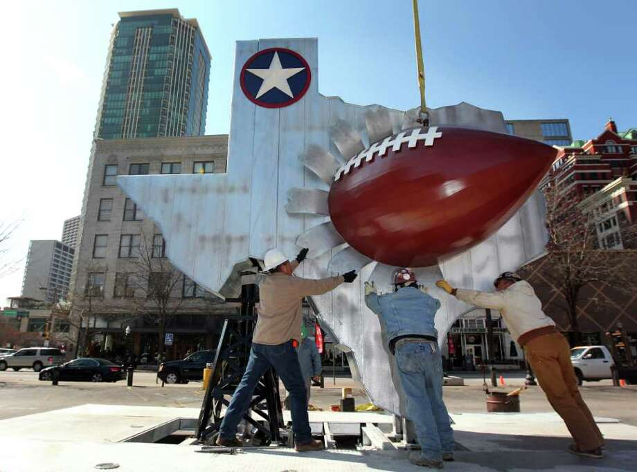 "Workers install the ""Cradle of Champions"" sculpture at Sundance Square in Fort Worth, Texas, on Tuesday, Jan. 25, 2011, in preparation for NFL football's Super Bowl XLV. The sculpture has more than 2,000 names of NFL players who played high school football in Texas from 1911 to the present. (AP Photo/The Dallas Morning News, Michael Ainsworth) ** MANDATORY CREDIT  MAGS OUT  NO SALES  TV OUT  INTERNET: AP MEMBERS ONLY ** Photo: Michael Ainsworth, MBR / The Dallas Morning News"