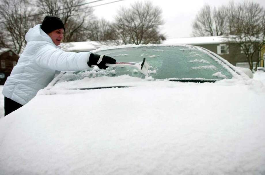Aniela Savona clears off her car in Norwalk on Tuesday, February 2, 2011. Photo: Lindsay Niegelberg / Connecticut Post