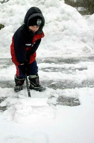Aidan Carlan, 6, helps shovel the driveway in Norwalk on Tuesday, February 2, 2011. Photo: Lindsay Niegelberg / Connecticut Post
