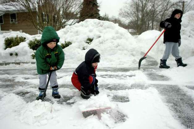 Brothers Matthew Carlan, left, and Aidan, center, help shovel the driveway as Jack, 11, carries a larger shovel to do some of the heavy lifting in Norwalk on Tuesday, February 2, 2011. While clearing driveway the brothers held a spirited debate over the weather, with Matthew, 4, insisting it was snowing, Aidan, 6, insisting it was raining, and Jack explaining the definition of sleet. Photo: Lindsay Niegelberg / Connecticut Post