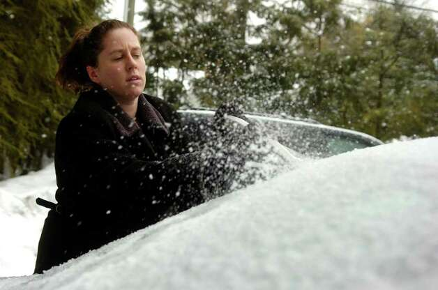 Jennifer Car clears the ice from her windsheild after being let off work early to avoid the ice in Westport on Tuesday, February 2, 2011. Photo: Lindsay Niegelberg / Connecticut Post