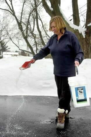 Kristin Holland sprinkles salt on her driveway in Fairfield on Tuesday, February 2, 2011. Photo: Lindsay Niegelberg / Connecticut Post