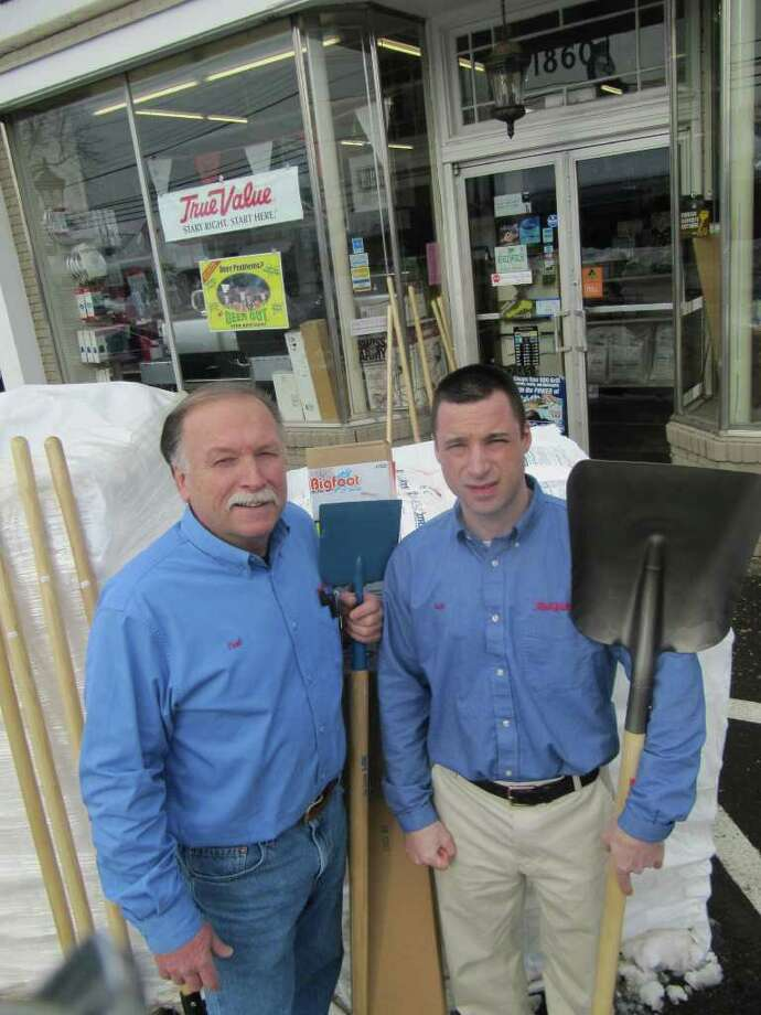 Fred Pesavento, owner of Hemlock Hardware, and son Scott, the store's manager, pose with some of the winter items that customers can't seen to get enough of this season. Such items include ice choppers, shovels, calcium chloride (stacked behind the Pesaventos) and roof rakes, one of which is partially blocked by an ice chopper in this photo. Photo: Kirk Lang / Fairfield Citizen