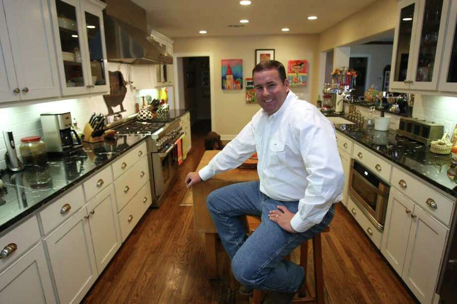White-veined black granite countertops and distressed white cabinets give a clean look to John Canavan's kitchen. Photo: HELEN L. MONTOYA, SAN ANTONIO EXPRESS-NEWS / hmontoya@express-news.net