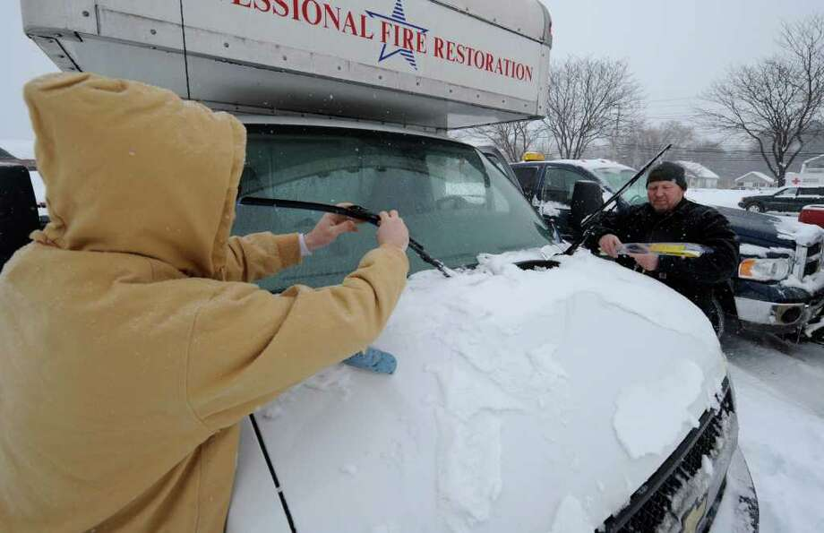 Steve Jacques and Dave Bowles of Professional Fire Restoration Service replace wiper blades on their company vehicle Tuesday.  (Skip Dickstein / Times Union) Photo: Skip Dickstein