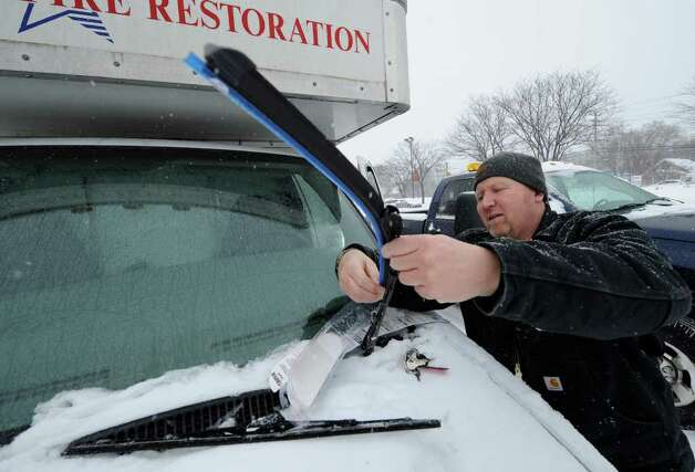 Dave Bowles of Professional Fire Restoration Service replaces the wiper blades on his company vehicle with new winter blades February 1, 2011.    (Skip Dickstein/Times Union) Photo: Skip Dickstein