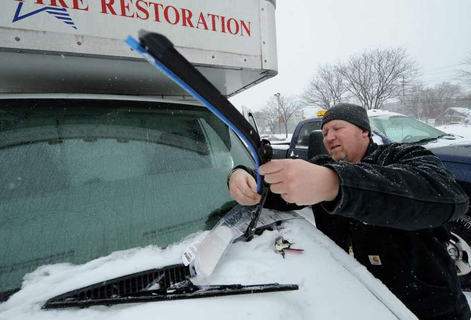 Dave Bowles of Professional Fire Restoration Service replaces the wiper blades on his company vehicle Tuesday.  (Skip Dickstein / Times Union) Photo: Skip Dickstein