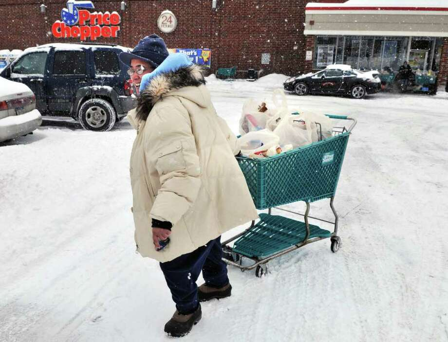 Toni Vidal of Albany drags a full shopping cart though the snow as she stocks up on groceries Tuesday at Price Chopper on Delaware Avenue in Albany.  (John Carl D'Annibale / Times Union) Photo: John Carl D'Annibale / 0202_weather
