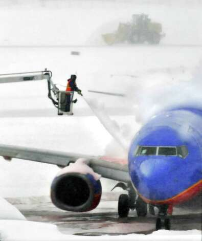 Ground crews de-ice an airliner as snowplows keep runways clear  Tuesday morning at Albany International Airport in Colonie. (John Carl D'Annibale / Times Union) Photo: John Carl D'Annibale / 0202_weather