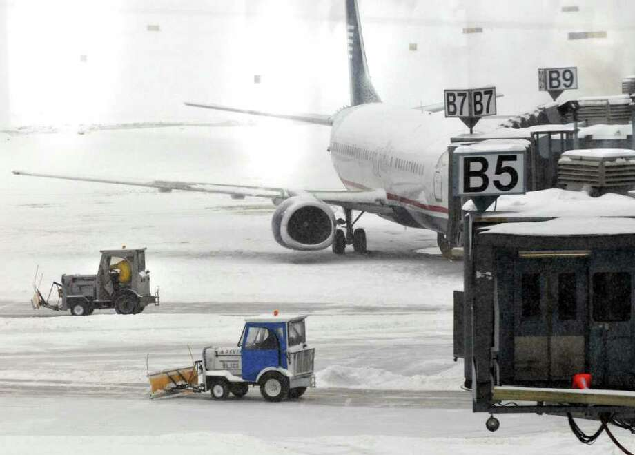 Crews clear snow Tuesdy from passenger gates at  Albany International Airport in Colonie. (John Carl D'Annibale / Times Union) Photo: John Carl D'Annibale / 0202_weather