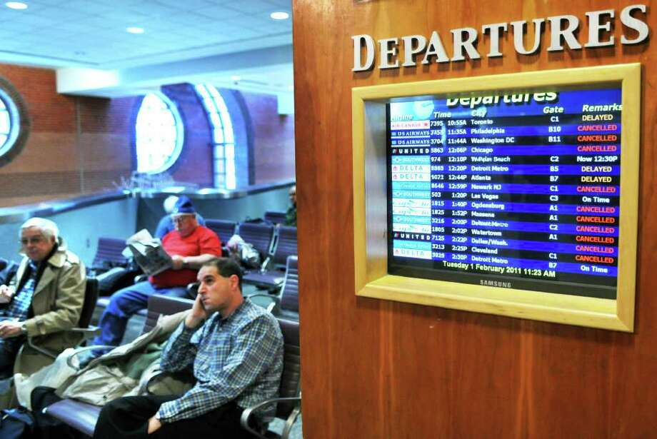Passengers Tuesday morning resign themselves to long waits at Albany International Airport in Colonie.  (John Carl D'Annibale / Times Union) Photo: John Carl D'Annibale / 0202_weather