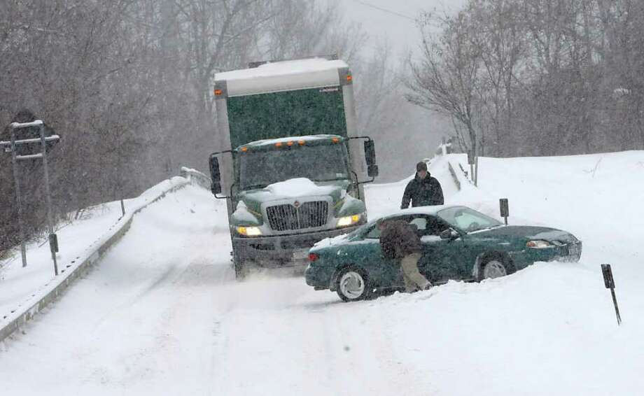 A car that slid off the road Tuesday blocks traffic on the ramp from Western Avenue and Schoolhouse Road to I-87 in Guilderland. ( Lori Van Buren / Times Union) Photo: Lori Van Buren