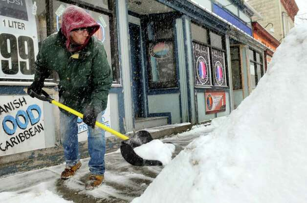 George Scott clears snow in front of New York Supermarket during a snow storm on Tuesday, Feb. 1, 2011, in Albany, N.Y. (Cindy Schultz / Times Union) Photo: Cindy Schultz