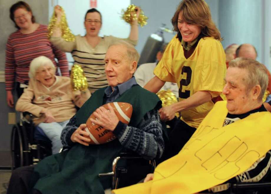 Employee Tracie Dott, right, pushes resident Frank Gorman of the Sackers team to a touchdown during the Wheelchair Super Bowl VIII against the Wheelers on Tuesday, Feb. 1, 2011, at the Teresian House in Albany, N.Y.  (Cindy Schultz / Times Union) Photo: Cindy Schultz