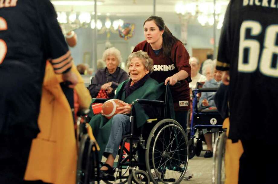 Social worker Lauren Bisio, center, assists resident Rose Italiano of the Sackers team during their Wheelchair Super Bowl VIII against the Wheelers on Tuesday, Feb. 1, 2011, at the Teresian House in Albany, N.Y.  (Cindy Schultz / Times Union) Photo: Cindy Schultz