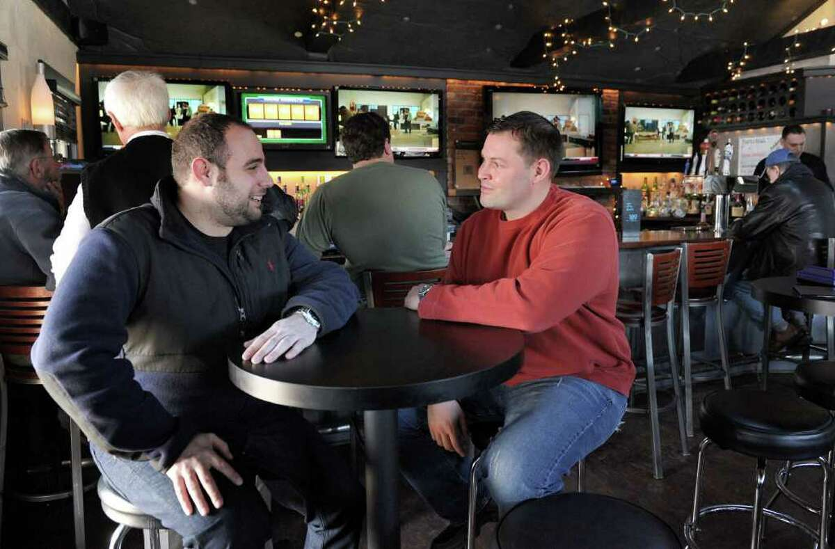 Eli Hawli, left, who co-owns 189 Sports Cafe with his brother Ayman, chats with customer Marc Anderson, right, of Brookfield. Photo taken Monday, January 31, 2011.