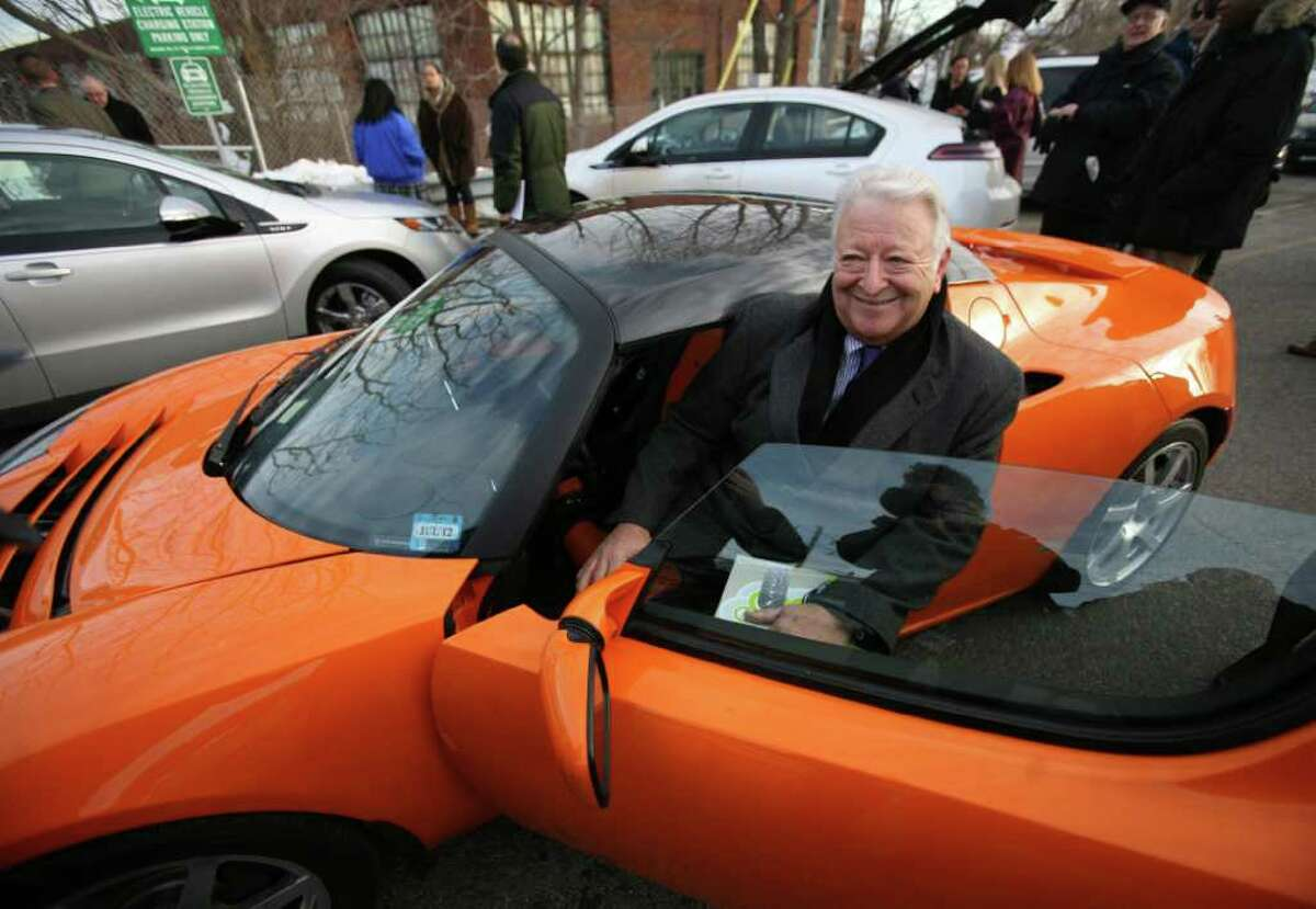 Norwalk Mayor Richard Moccia tries to squeeze into an electric 2010 Tesla Roaster Sport during a kickoff for the new electric vehicle charging stations at the South Norwalk Train Station on Monday, January 31, 2011.
