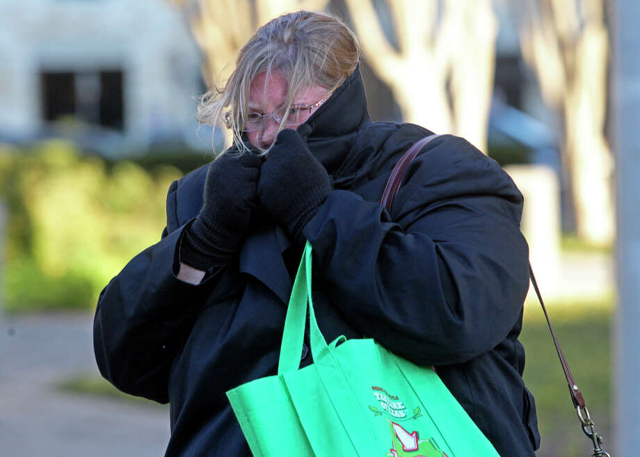 Liz Ermis shields herself from the cold wind as she leaves work on Houston Street downtown. A wind advisory is in effect until 11 a.m. today. Photo: Tom Reel/treel@express-news.net / © 2010 San Antonio Express-News