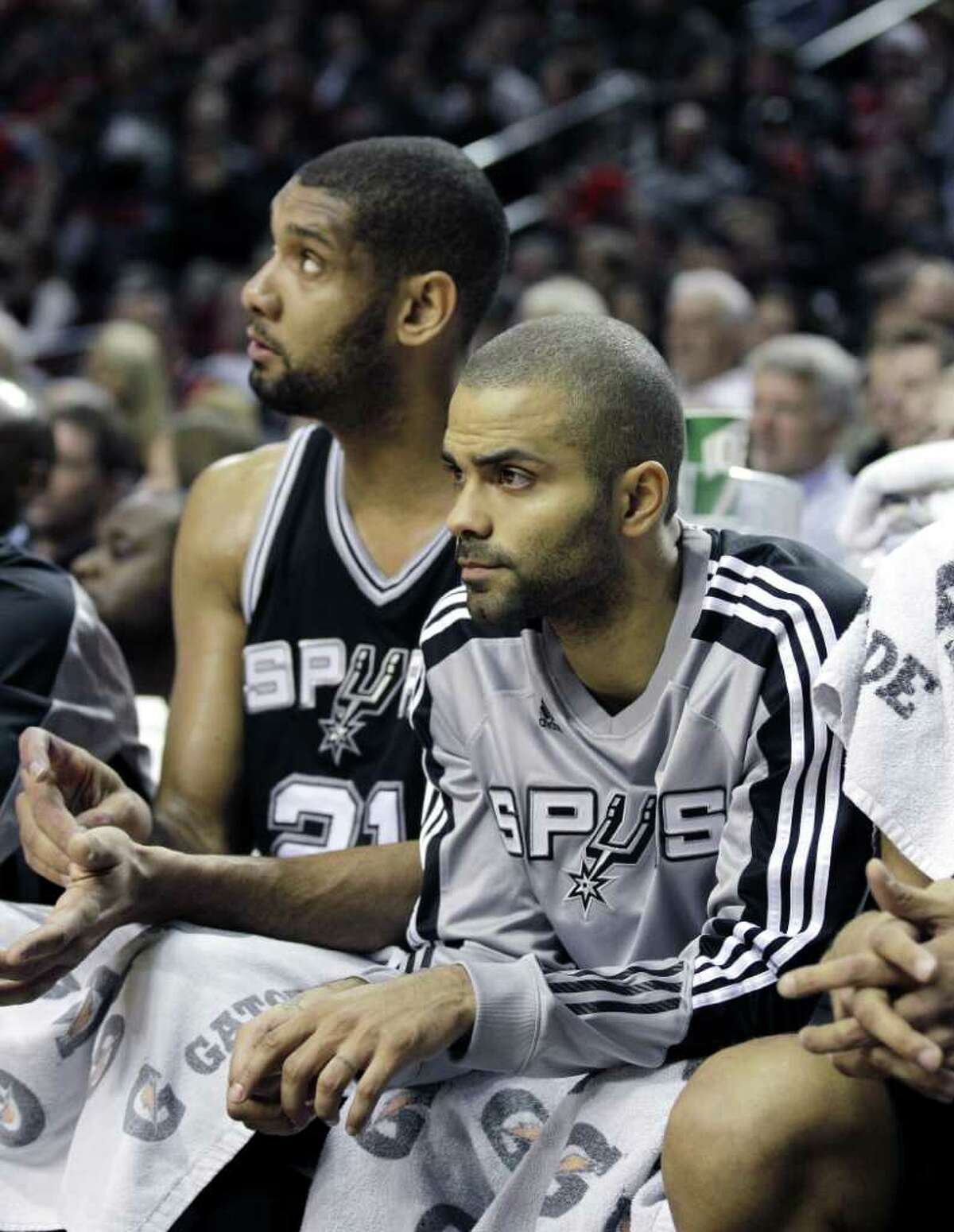 San Antonio Spurs' Tim Duncan, left, and Tony Parker look on from the bench in the first half during an NBA basketball game with Portland Trail Blazers Tuesday, Feb. 1, 2011, in Portland, Ore. The Trail Blazers defeated the Spurs 99-86.