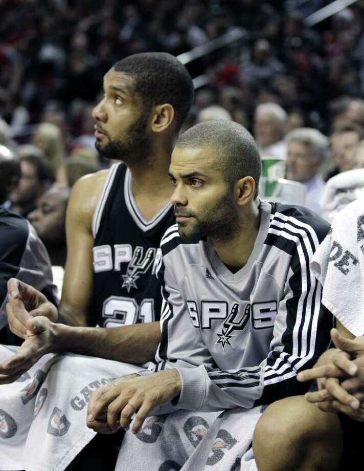 San Antonio Spurs' Tim Duncan, left, and Tony Parker look on from the bench in the first half during an NBA basketball game with Portland Trail Blazers Tuesday, Feb. 1, 2011, in Portland, Ore. The Trail Blazers defeated the Spurs 99-86. Photo: AP
