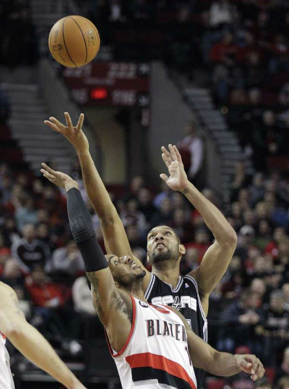 San Antonio Spurs' Tim Duncan, rear and Portland Trail Blazers' LaMarcus Aldridge look for a rebound in the first quarter during an NBA basketball game Tuesday, Feb. 1, 2011, in Portland, Ore.