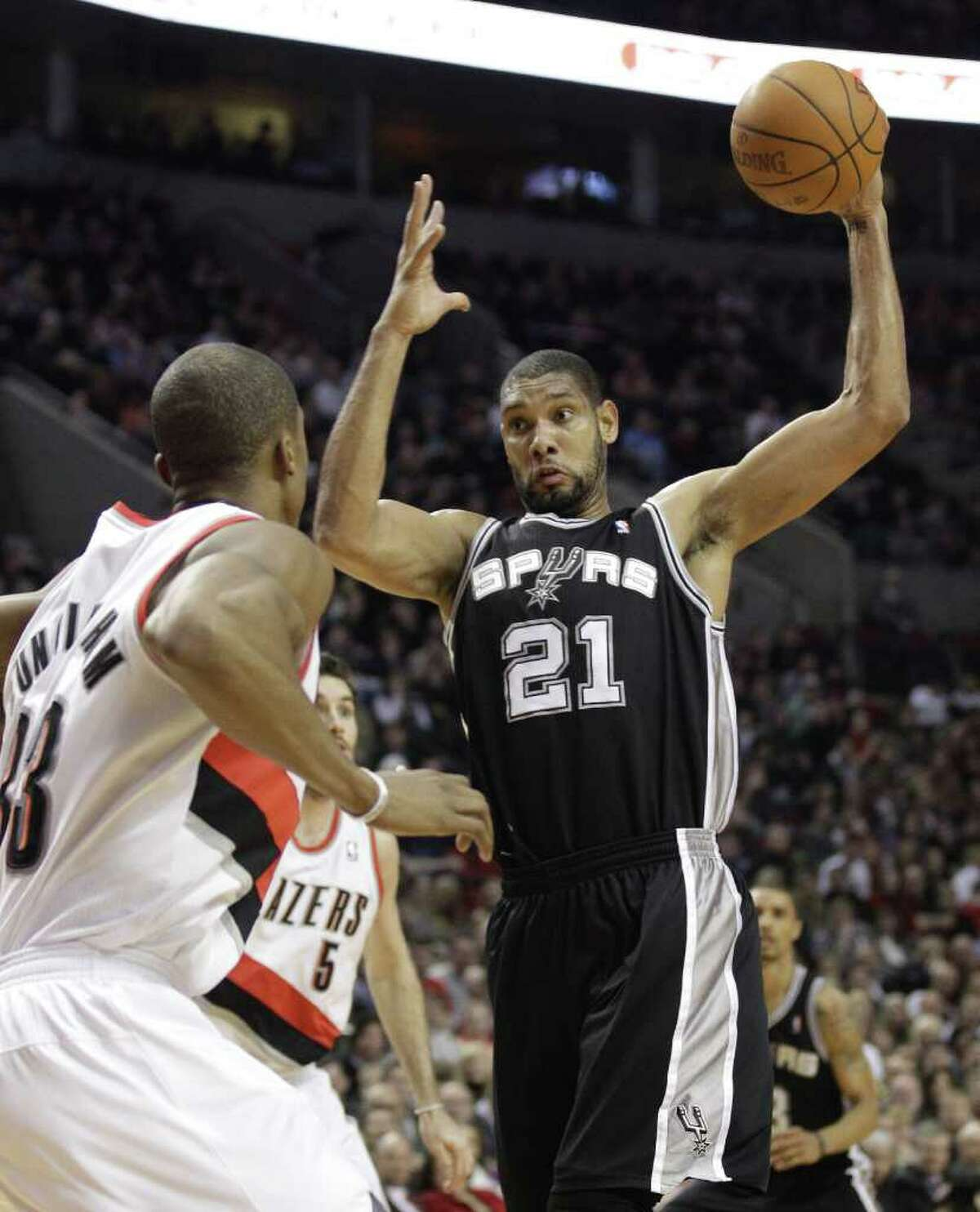 San Antonio Spurs' Tim Duncan (21) pulls down a rebound as Portland Trail Blazers' Dante Cunningham (33) looks on in the first quarter during an NBA basketball game Tuesday, Feb. 1, 2011, in Portland, Ore.