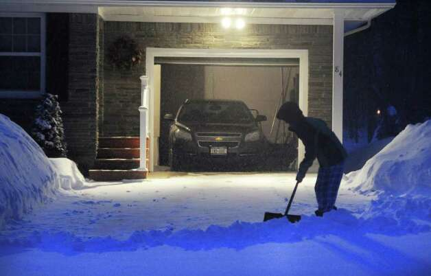 As the region wakes to another winter storm, a woman shovels snow from her driveway in Saratoga Springs Wednesday morning.   (Skip Dickstein / Times Union) Photo: SKIP DICKSTEIN / 2008