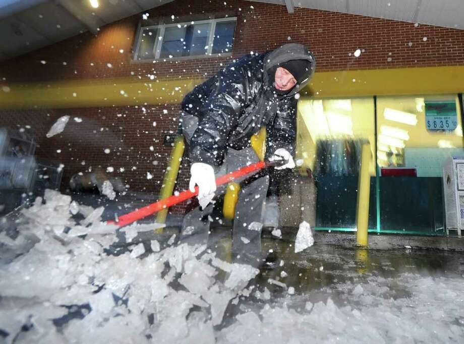 Mobil On The Run employee, Augusto Osorio, breaks ice on the pavement in front of the gas station on East Putnam Avenue, Old Greenwich, during the  ice storm that hit the area, Wednesday morning, Feb. 2, 2011. Photo: Bob Luckey / Greenwich Time