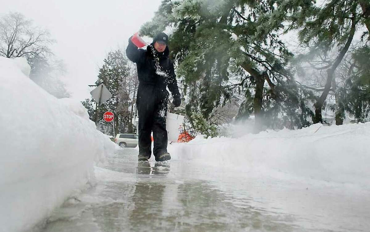Marcos Bertipaglia spreads salt along a sidewalk on Summer Street as snow, ice and rain hit the area in Stamford, Conn. on Wednesday February 2, 2011.