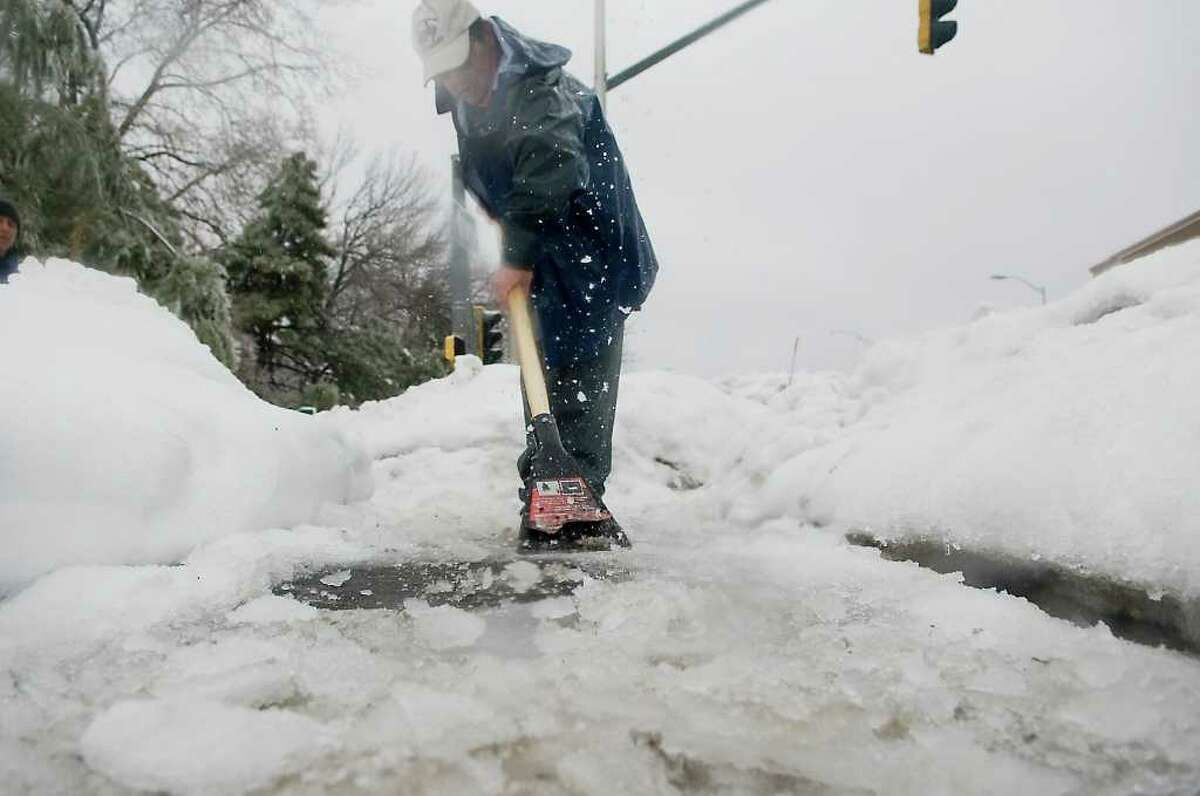 A man chips ice from a sidewalk on Summer Street as snow, ice and rain hit the area in Stamford, Conn. on Wednesday February 2, 2011.