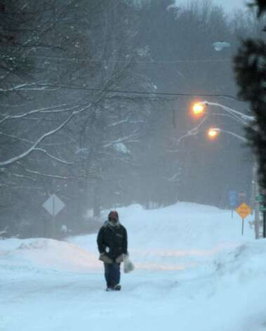 A pedestrian heads down Jefferson Street in the predawn hours Wednesday in Saratoga Springs. (Skip Dickstein / Times Union) Photo: SKIP DICKSTEIN / 2008