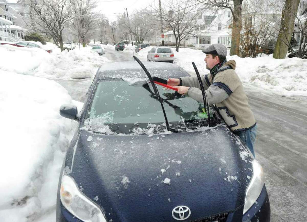 Noel Houlihan clears ice from his car in front of his central Greenwich home during the ice storm that hit the area, Wednesday morning, Feb. 2, 2011.
