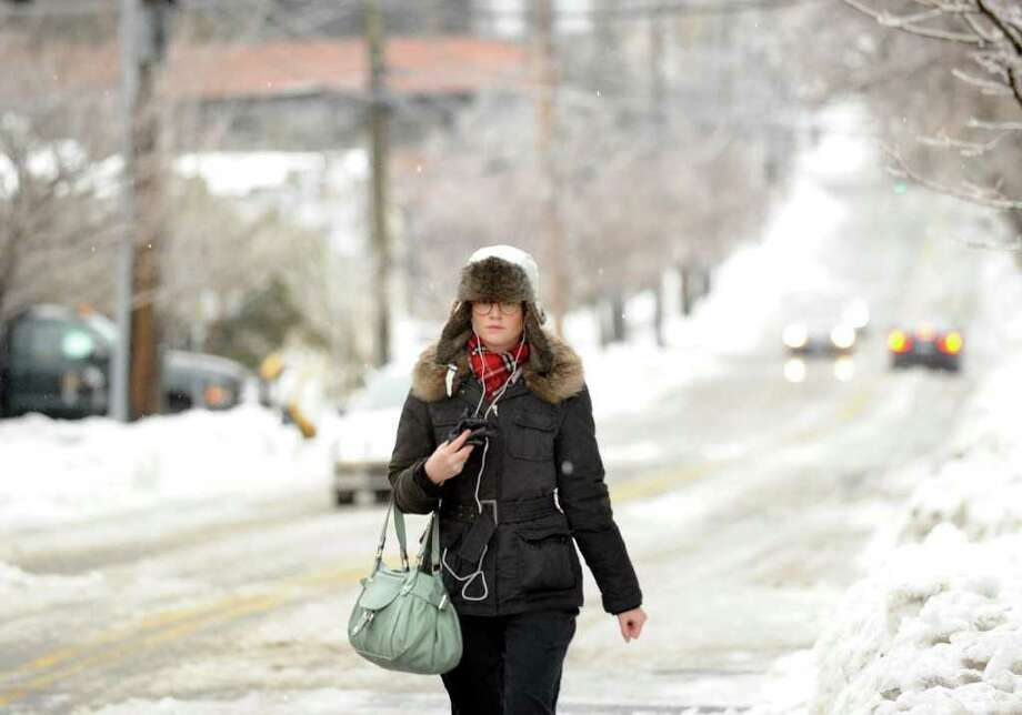 A woman walks on an icy East Elm Street, Greenwich, during the ice storm that hit the area, Wednesday morning, Feb. 2, 2011. Photo: Bob Luckey / Greenwich Time